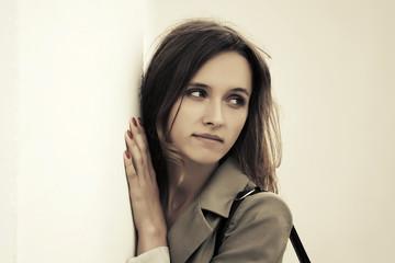 Sad young fashion woman at the wall