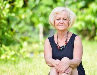 Mature, blonde woman in garden,