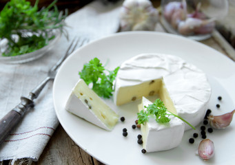 Camembert cheese with herbs on a white plate for appetizer