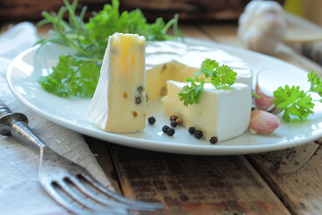 Plate with french camembert cheese with fresh herbs and spices