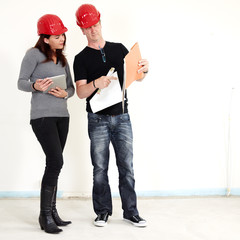 Architect and customer making plans in building lot