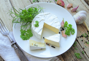 Camembert cheese on a white plate with fresh herbs