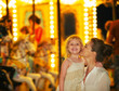 Portrait of happy mother and baby girl in front of carousel