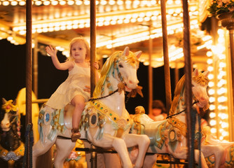 Portrait of happy baby girl riding on carousel
