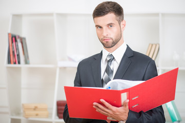 Portrait of handsome confident businessman standing in office wi
