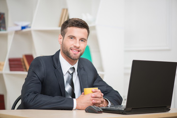 Portrait of handsome businessman enjoying the coffee-break sitti