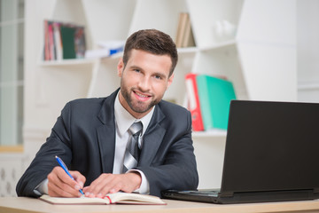 Portrait of handsome confident businessman writing in red notebo