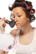 happy housewife with curlers to apply makeup on her face