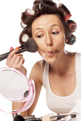 happy housewife with curlers to apply makeup on her cheeks