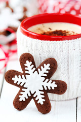 Snowflake Christmas cookie with cup of cappuccino