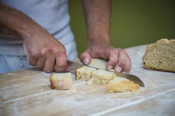 Panadero cortando un trozo de pan recién hecho en el obrador