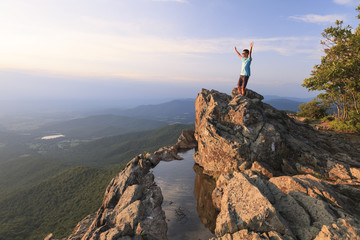 A teenager standing on the edge of a cliff