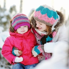Young mother and her daughter at winter