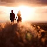 Fototapety Young couple enjoying the sunset