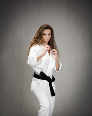 girl with uniform and black belt ready to defense