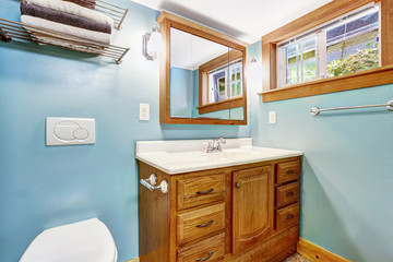 Blue bathroom interior with wooden vanity cabinet