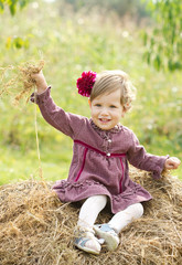 Smiling little country girl on haystack