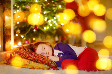 Little girl sleeping under the Christmas tree