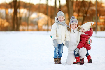 Mother and her daughters having fun on winter day
