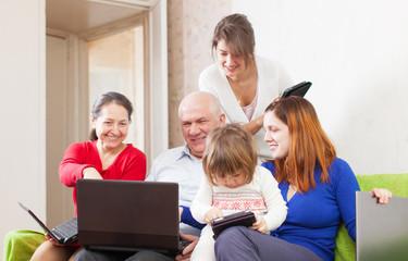 family enjoys on sofa in livingroom room with  laptops