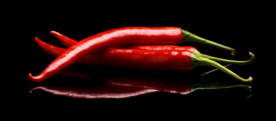 Red chilli peppers isolated on black background