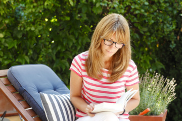Attractive woman reading in the garden