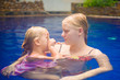 Young mother and adorable daughter having fun in pool