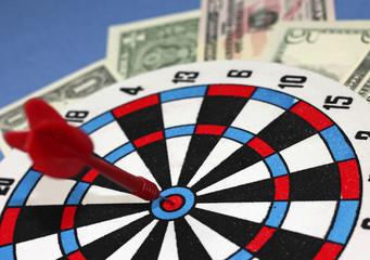 """Concept of wealth - dart hit at """"bull's eye"""""""
