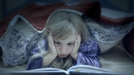 Little girl under bed sheets reading scared