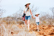 Mother and daughter hiking at scenic terrain