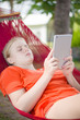 Young woman reading on electronic tablet reader relaxing in hamm