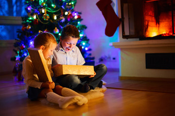 Kids at home on Christmas eve opening gifts