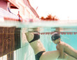Lessons of diving. Mother and her son in swimming pool swim