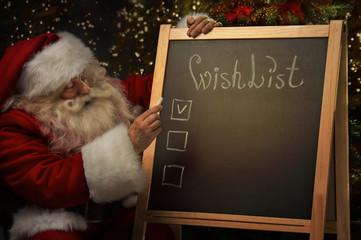 Santa Claus sitting near chalkboard with wishlist