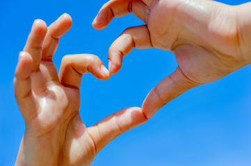 Heart hands in a clear sky