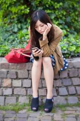junge Frau schaut gelangweilt auf ihr Smartphone