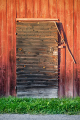 Old weathered black barn door with locks and shingles