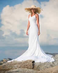 Beautiful and slim woman stand in white long dress