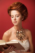 Portrait of redhead edwardian women with book on red background.