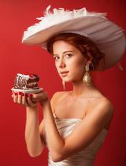 Portrait of redhead edwardian women with cake on red background.