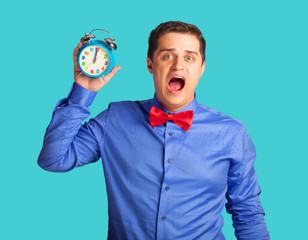 Handsome man with alarm clock on blue background.