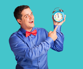 Casual man in shirt with alarm clock on blue background.