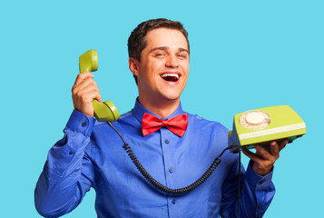 happy man with green telephone on blue background