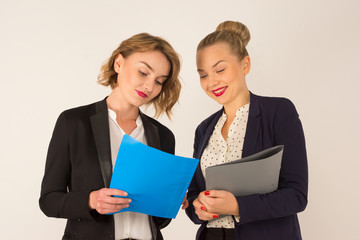 Two young women discussing documents