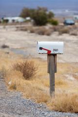 Cassetta delle lettere bianca in metallo con numero nel deserto