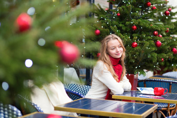 Girl writing Christmas postcards in a cafe