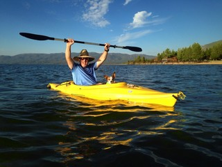 Athletic man kayaking on Lake Tahoe with dog.