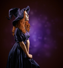 beautiful red-haired girl in  costumes witch