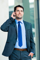 Confident businessman outdoor using phone