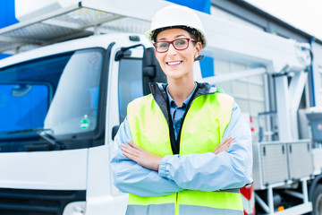 Kranfahrerin vor Kranwagen einer Baustelle